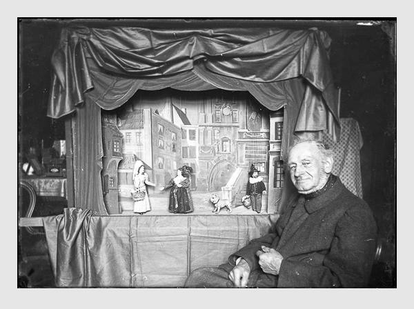 Valeska Kollmann: Joseph Leonhard Schmid hinter seiner Marionettenbühne mit Harlekin und Kasperl Larifari. München, 1900. Der ins Positiv umgewandelte Scan vom Originalfilm aus der Sammlung Kollmann, späterer Sammlung Link, wurde freundlicherweise von Staatliche Kunstsammlungen Dresden zur Verfügung gestellt.